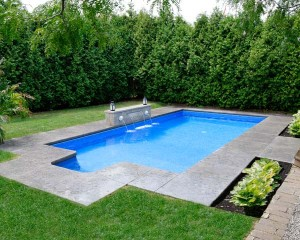 Square shaped swimming pool with tall trees