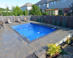Square shaped inground pool with patio area