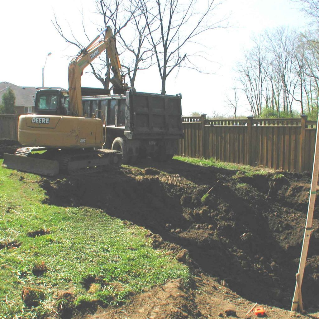 Excavator digging a back yard and loading a dump truck