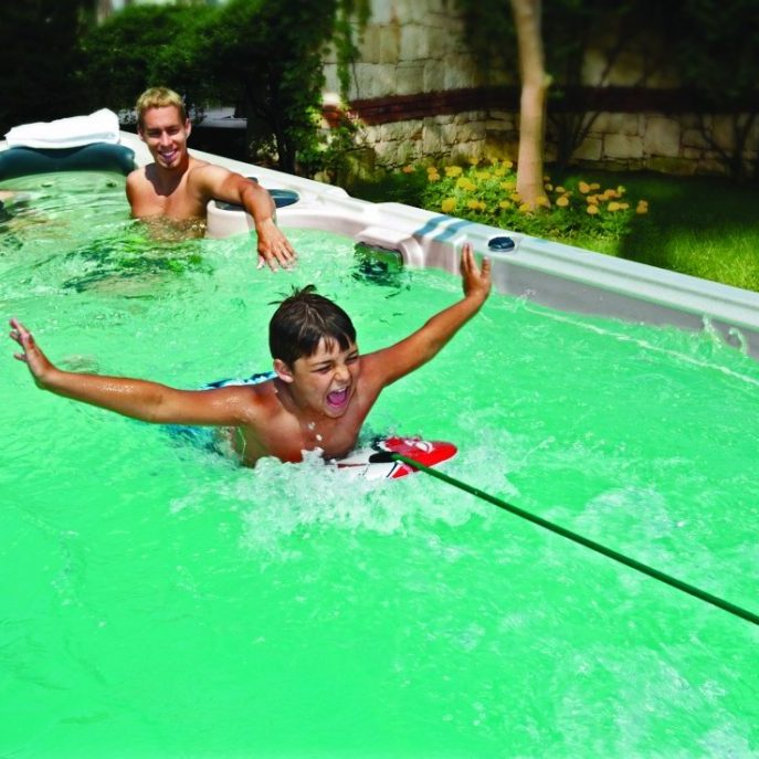 Young boy riding a boogie boy tethered to a swim spa